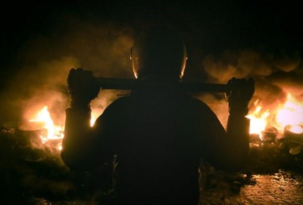 Повстанец с битой на фоне горящих покрышек